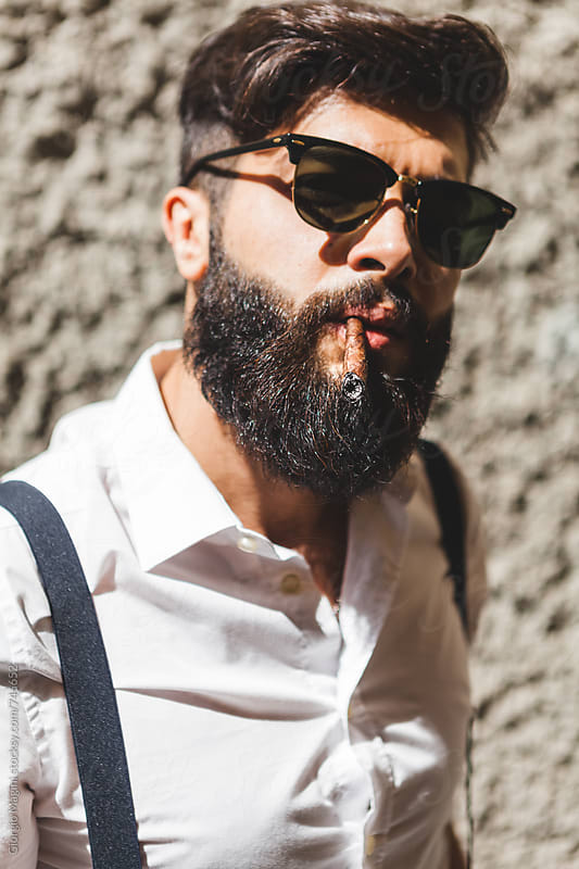 Portrait of a Young Bearded Man Smoking a Cigar by Giorgio Magini for Stocksy United