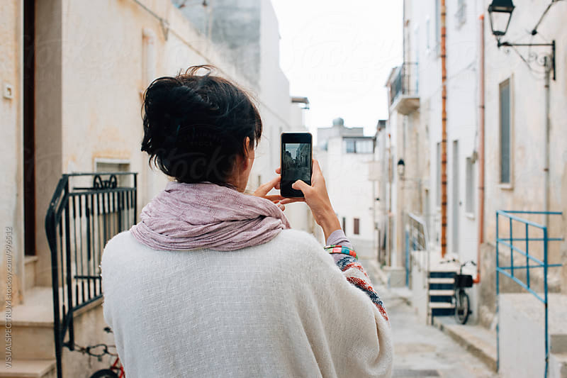 Brunette Woman in White Poncho Taking Cellphone Photo in Whitewashed Italian Village by Julien L. Balmer for Stocksy United