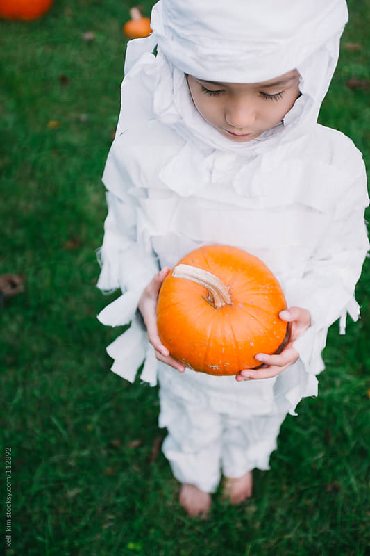 Young Child Dressed As Mummy Looks Down At Small Pumpkin In Hands by kelli kim for Stocksy United