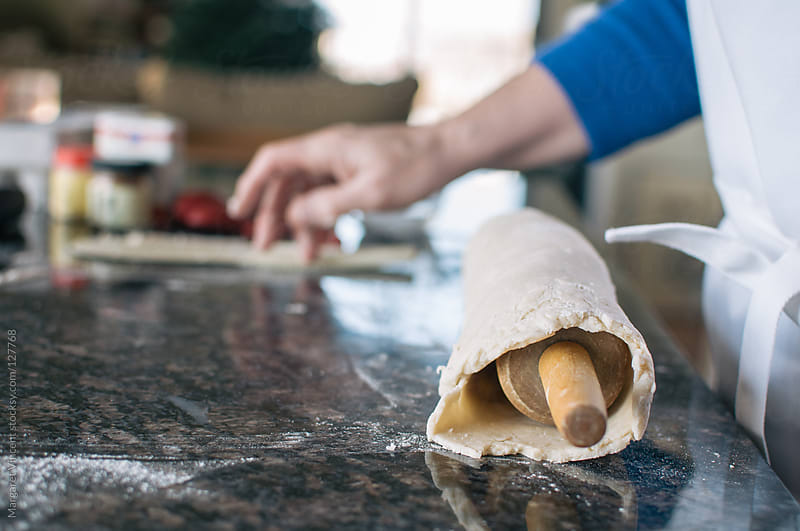 pie crust rolled around a rolling pin by Margaret Vincent for Stocksy United