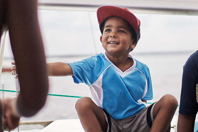 Young smiling black boy on a sailboat by Per Swantesson for Stocksy United
