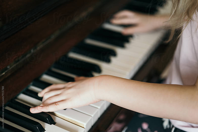 child playing in piano by Javier Pardina for Stocksy United