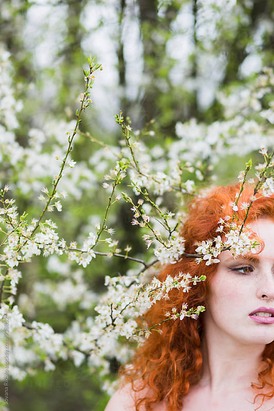 Ginger haired young woman in cherry blossom by Jovana Rikalo for Stocksy United
