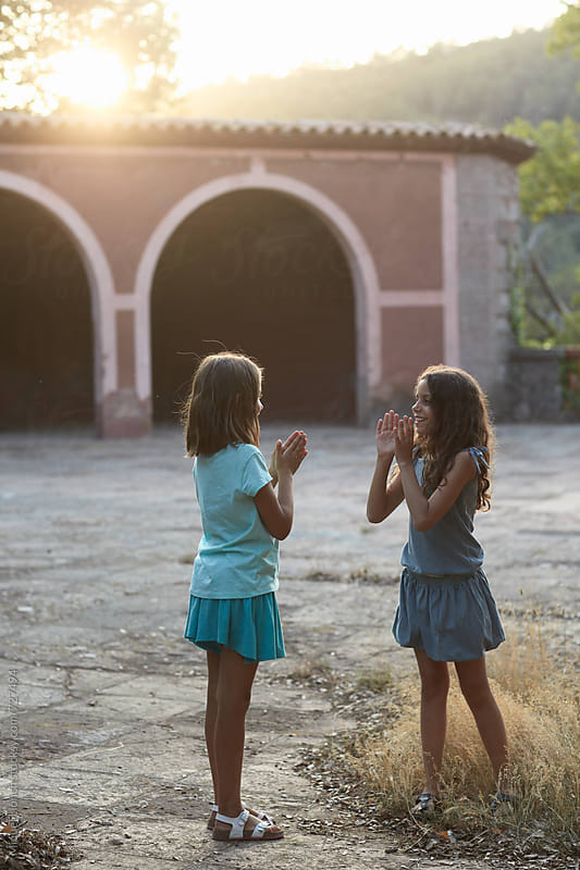 Two young girls playing outdoors at the sunset by Miquel Llonch for Stocksy United
