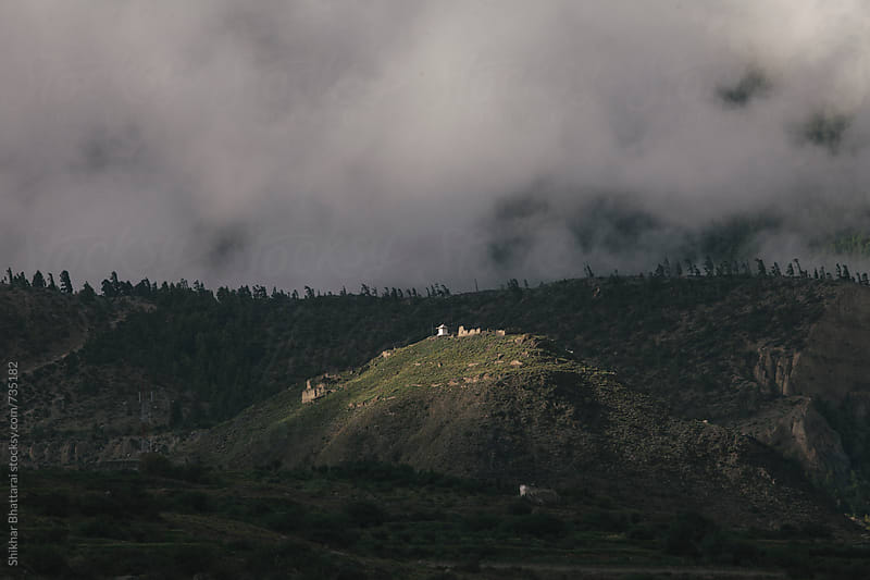 A chorten atop a hill lit up by the first rays of the day. by Shikhar Bhattarai for Stocksy United