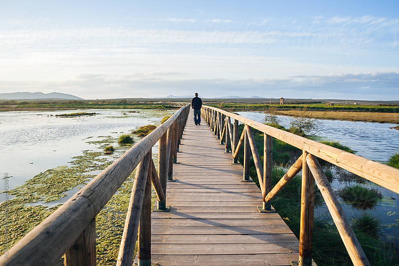 Man walking along a wooden walkway by ACALU Studio for Stocksy United