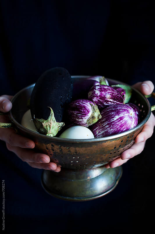Hands holding old copper colander with brinjals or eggplants by Nadine Greeff for Stocksy United