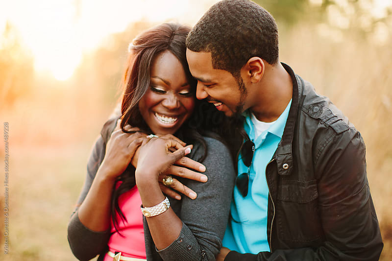 A young African American couple outdoors in a loving embrace by Kristen Curette Hines for Stocksy United