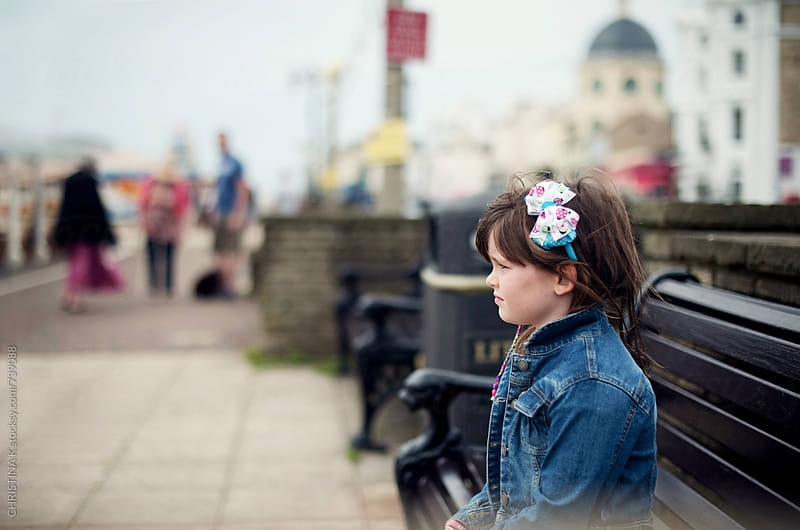 Girl sitting on a bench on the seafront by CHRISTINA K for Stocksy United