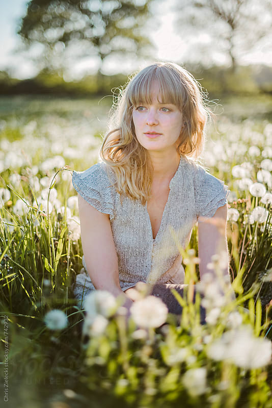 a girl sitting in a meadow with dandelions by Christian Zielecki for Stocksy United