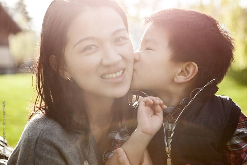 Asian boy kissing his mother by Suprijono Suharjoto for Stocksy United