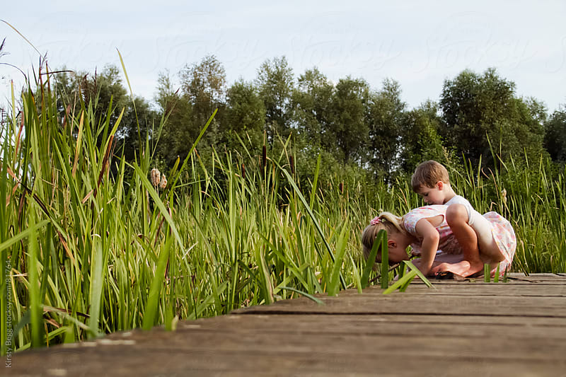 Boy and girl by reeds in nature reserve by Kirsty Begg for Stocksy United