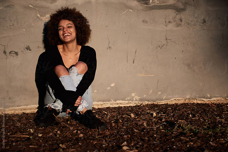 Young smiling woman with afro laughing by Guille Faingold for Stocksy United