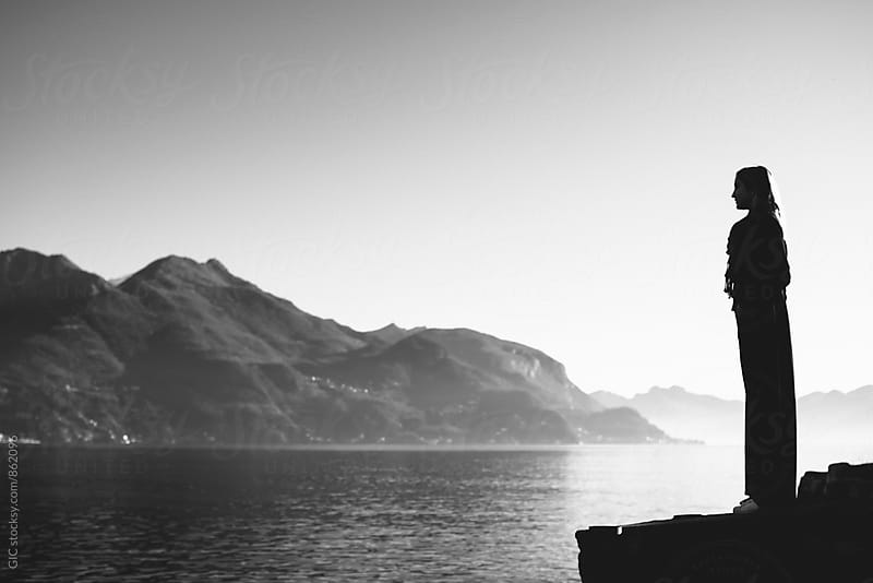 Silhouette of woman standing against the lake by Simone Becchetti for Stocksy United