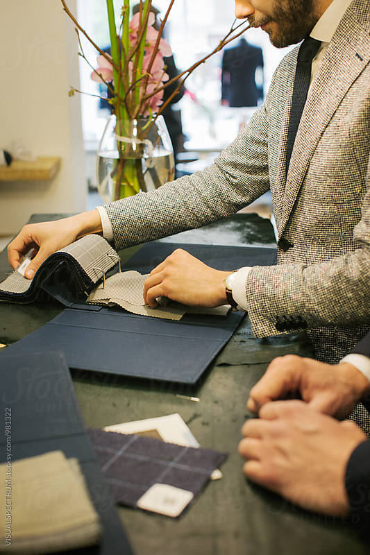 Men's Fashion - Close Up of Two Young Caucasian Men in Suits Looking at Suit Fabrics by Julien L. Balmer for Stocksy United