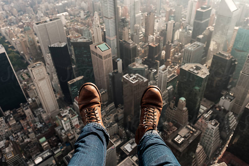 A Man's Feet Dangle Outside of a Helicopter as it Flies Over Manhattan. by Riley J.B. for Stocksy United