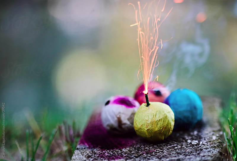 Blue, yellow and orange smoke bombs with the yellow one lit. by Carolyn Lagattuta for Stocksy United