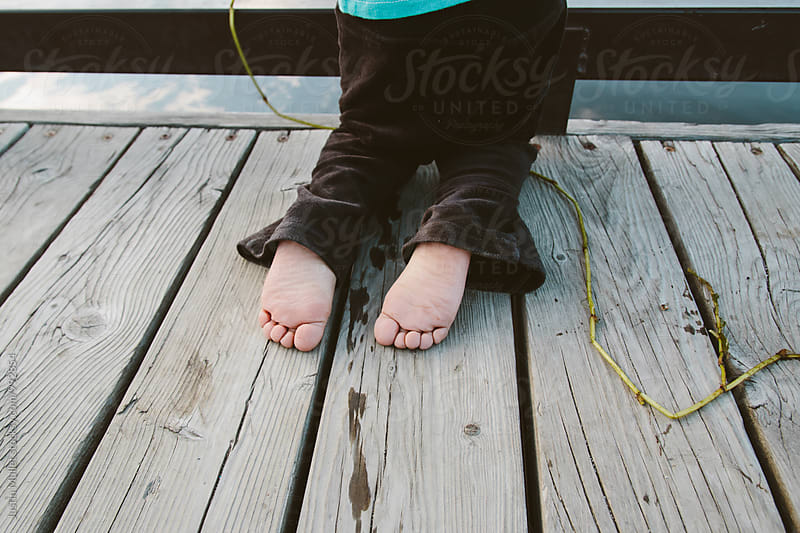 Barefeet of toddler girl kneeling on a boat dock by Justin Mullet for Stocksy United