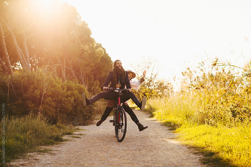 Young hipster couple having fun on a bicycle in the forest. by BONNINSTUDIO for Stocksy United
