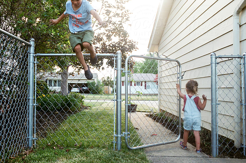 girl walks out fence while brother jumps by Maria Manco for Stocksy United
