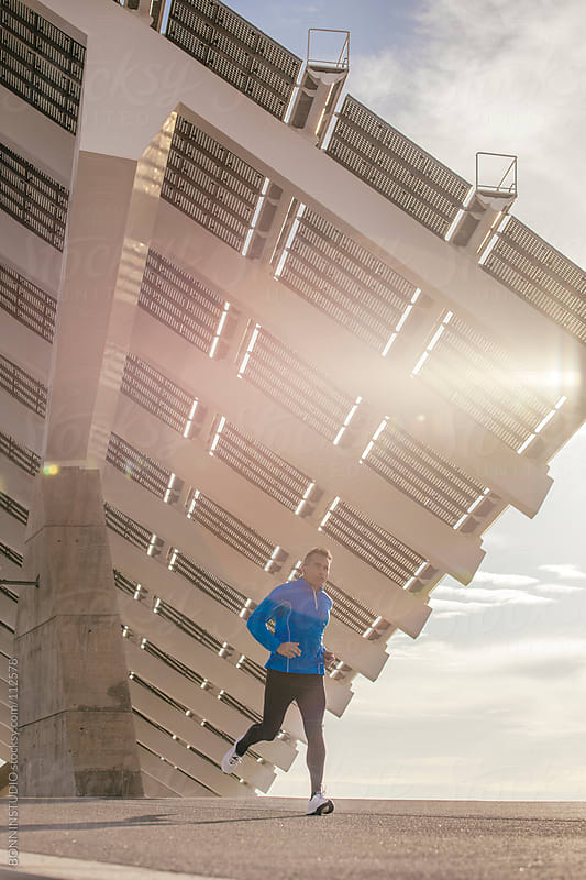 Man running and listenning music under big solar panel.  Sunset light effect. by BONNINSTUDIO for Stocksy United
