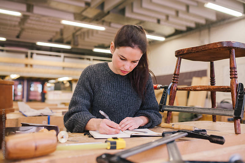 Female woodworker working on a bench, drawing her design before starting to work by Ivo de Bruijn for Stocksy United