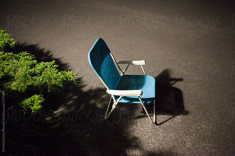 Chair in parking lot at night by Christine Hewitt for Stocksy United