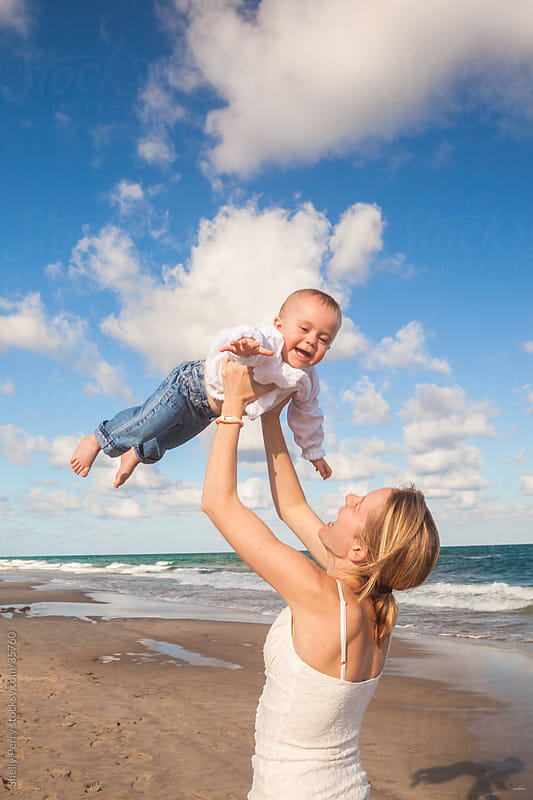Mom Holding Toddler Aloft to the Sky at the Beach by Shelly Perry for Stocksy United