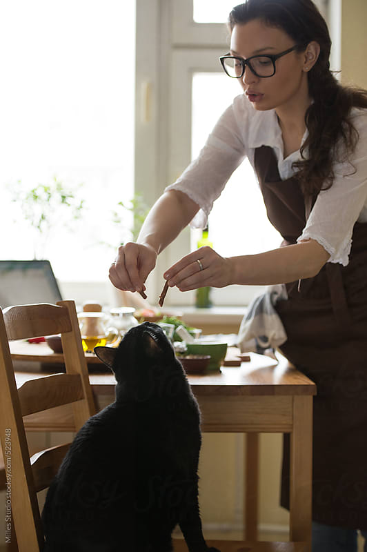 Woman feeding her cat while cooking at home by Milles Studio for Stocksy United