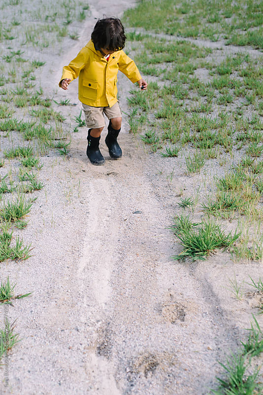 boy in rain jacket and boots jumping in a non-puddle by Tara Romasanta for Stocksy United