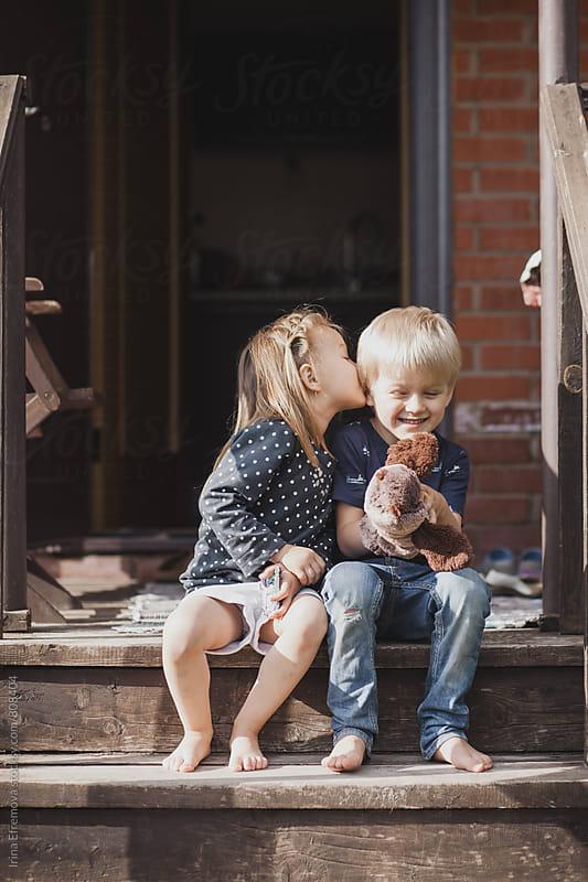 Boy and a girl sitting on a porch by Irina Efremova for Stocksy United