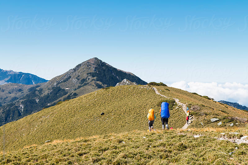 People hiking on the footpath toward mountain peak by Lawren Lu for Stocksy United