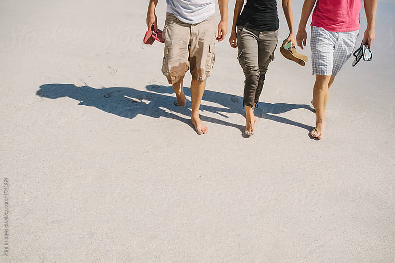 Friends walking along the beach by Aila Images for Stocksy United