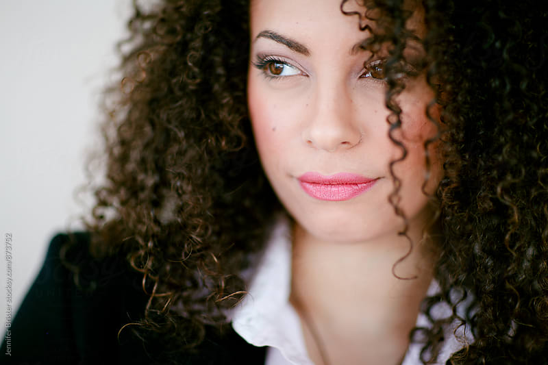 Close up of beautiful woman with curly hair by Jen Brister for Stocksy United