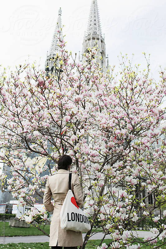 Back view of a young woman standing in front of a big magnolia tree by Jovana Rikalo for Stocksy United