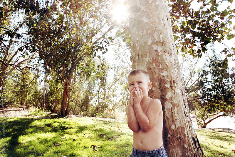 Boy in Park Giggling Covering His Mouth by Dina Giangregorio for Stocksy United