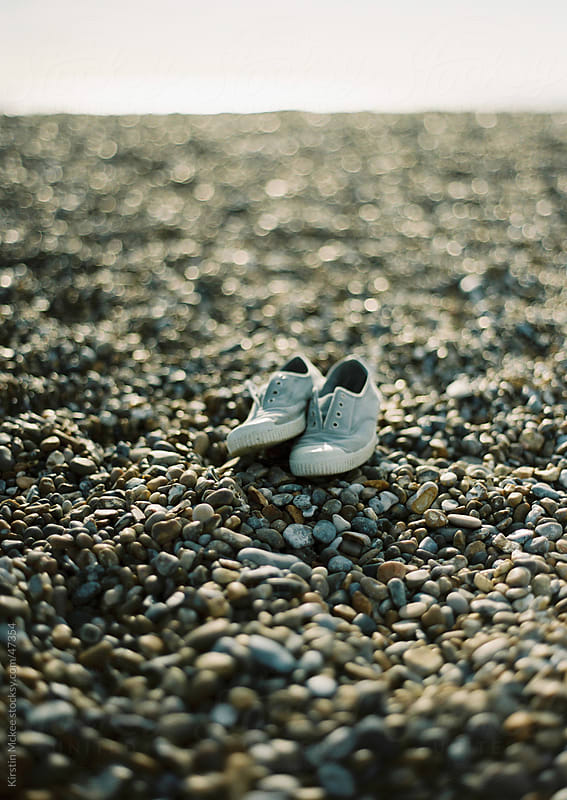Grey shoes on a stony beach.  by Kirstin Mckee for Stocksy United