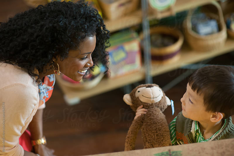 Mother talks with excited son at toy store checkout counter by Brian McEntire for Stocksy United