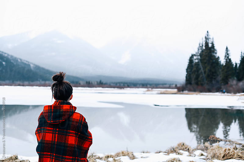 Young woman looks out across frozen lake by Treasures & Travels for Stocksy United