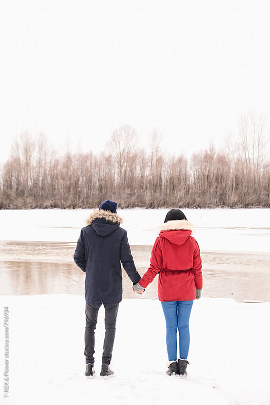 Couple of young man and woman standing on winter coast  by Danil Nevsky for Stocksy United