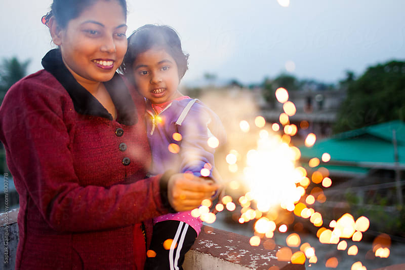 Mother and daughter having fun with sparkler by Saptak Ganguly for Stocksy United