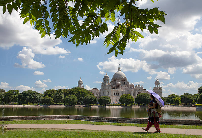 A woman walking in front of Victoria Memorial hall,Kolkata by PARTHA PAL for Stocksy United