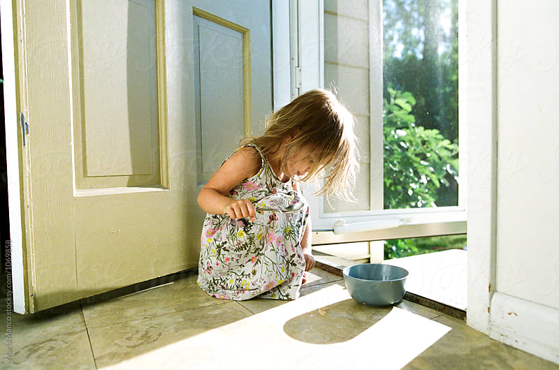 little girl eats bowl of cereal in sunshine by Maria Manco for Stocksy United