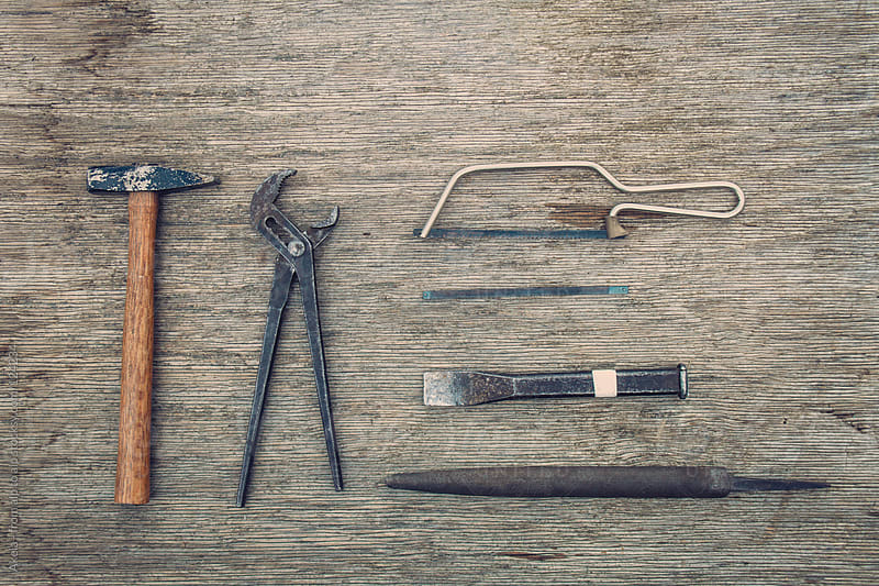 old rusty tools on wooden background by Leander Nardin for Stocksy United