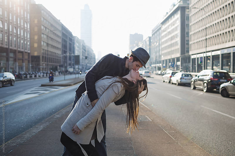 Young couple kissing passionately in the street by michela ravasio for Stocksy United