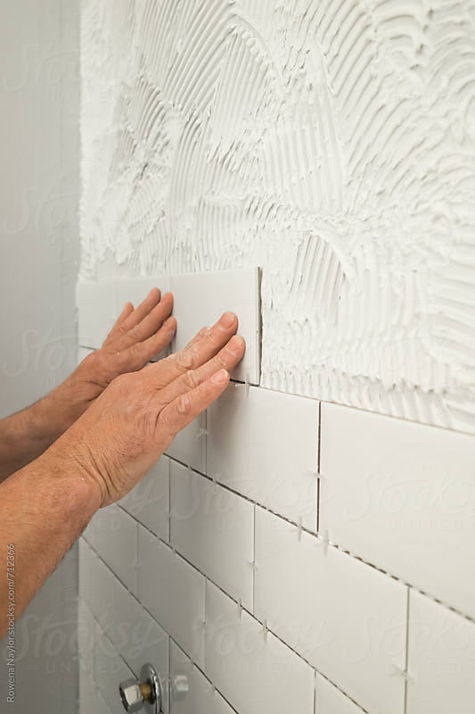 Man laying white tiles in bathroom shower by Rowena Naylor for Stocksy United