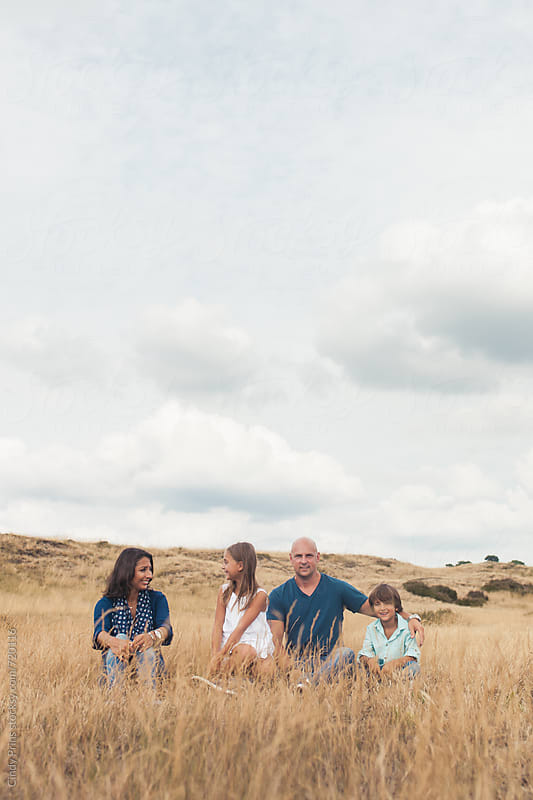 Family of four sitting in a golden field underneath a big cloudy sky by Cindy Prins for Stocksy United