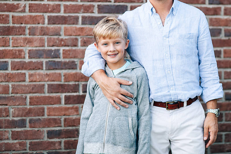 smiling boy embraced by his father  by Kelly Knox for Stocksy United