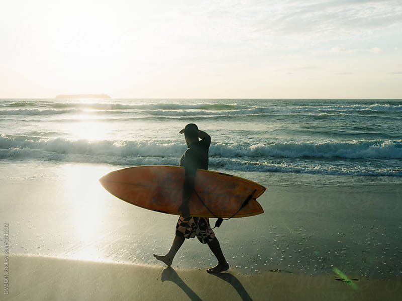 Surfer walking on beach with his board by DV8OR for Stocksy United