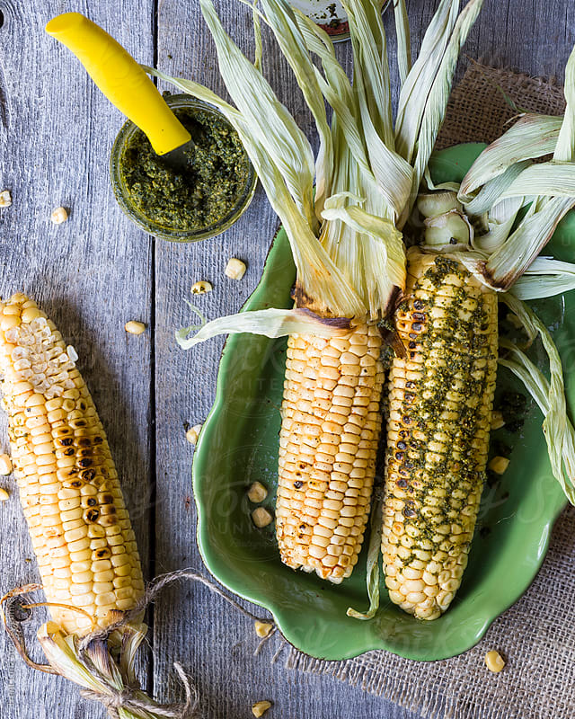 Three grilled pesto corn cobs  by Trent Lanz for Stocksy United